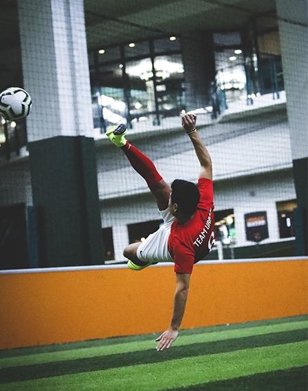 Joueur dans les airs qui frappe la balle